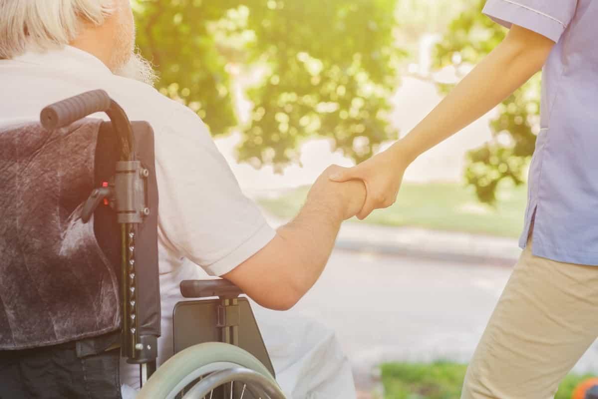 車椅子患者に寄り添い手を差し伸べる